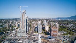 Aerial view of a big construction site at a mall with skytrain and appartment buildings in the vicinity. Taken in Burnaby, Vancouver City, British Columbia, Canada.@0.5x